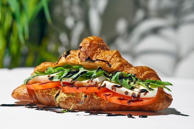 Сэндвич с круассаном с прошутто, клубникой, рукколой и бальзамическим соусом. жесткий свет. белый фон