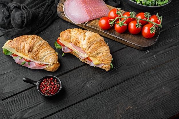 검은 나무 테이블 배경에 햄, 토마토, 치즈 세트, 허브와 재료, 텍스트 복사 공간 크로 샌드위치