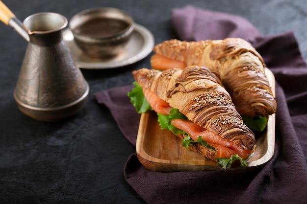 Круассан сэндвич с лососем и листьями салата