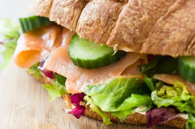 Круассан бутерброд с лососем и овощами на деревянный стол