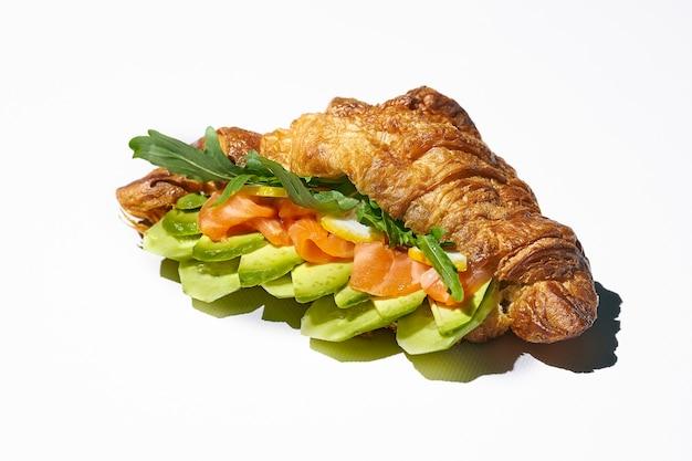 Сэндвич с круассаном с лососем, рукколой и авокадо. жесткий свет. белый фон