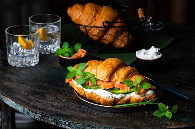 Сэндвич с круассаном с малосольным лососем на черной тарелке, подается со свежими листьями базилика, авокадо и сыром филадельфия. французский завтрак. концепция здорового питания.