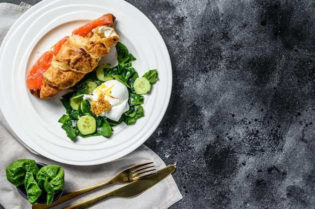Сэндвич с круассаном и соленым лососем, подается со свежими листьями салата, шпинатом, яйцом и овощами. черная поверхность. вид сверху. копировать пространство