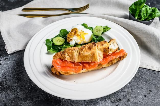 Сэндвич с круассаном и соленым лососем, подается со свежими листьями салата, шпинатом, яйцом и овощами. черная поверхность. вид сверху
