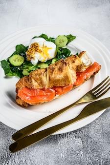 Сэндвич с круассаном и соленым лососем, подается со свежими листьями салата, шпинатом, яйцом и овощами. серая поверхность. вид сверху