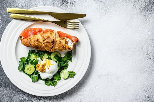 Сэндвич с круассаном и соленым лососем, подается со свежими листьями салата, шпинатом, яйцом и овощами.