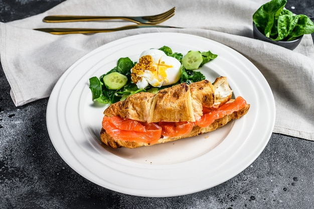 Croissant sandwich with salted salmon served with fresh salad leaves spinach, egg and vegetables. black surface. top view