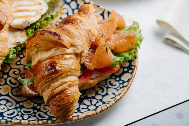 Croissant sandwich with smoked salmon and vegetables.