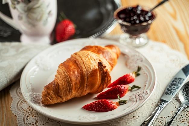 クロワッサンサンドイッチと木製のテーブルの上のコーヒーカップ