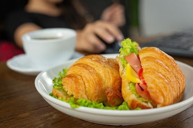 Croissant sandwiches on dark wooden surface