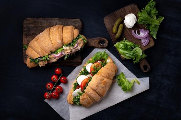黒の背景に木の板に新鮮な野菜と揚げ肉のクロワッサンサンドイッチ