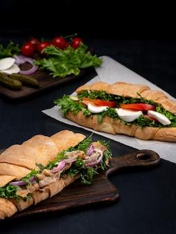 黒の木製の背景に新鮮な野菜とハムのクロワッサンサンドイッチ