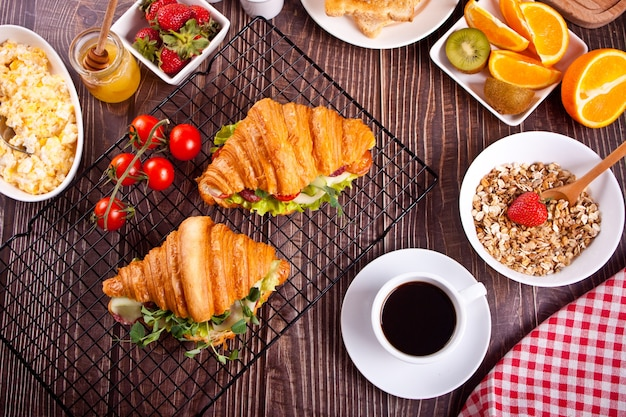 Croissant sandwiches with ham, cheese and greens. muesli, fruits and cup of coffee nearby