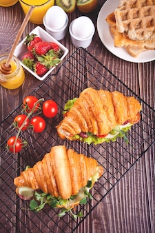Croissant sandwiches with ham, cheese greens with waffles, honey, strawberries and tomatos