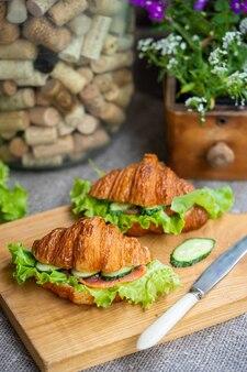 Бутерброды с круассаном с салатом из лосося и огурцом на деревянной доске