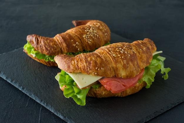 Бутерброды с круассаном с соленым лососем на столе, подается со свежими листьями салата, рукколой и овощами на черном фоне.
