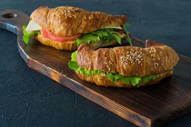 Бутерброды с круассаном и малосольным лососем на столе, подаются со свежими листьями салата,