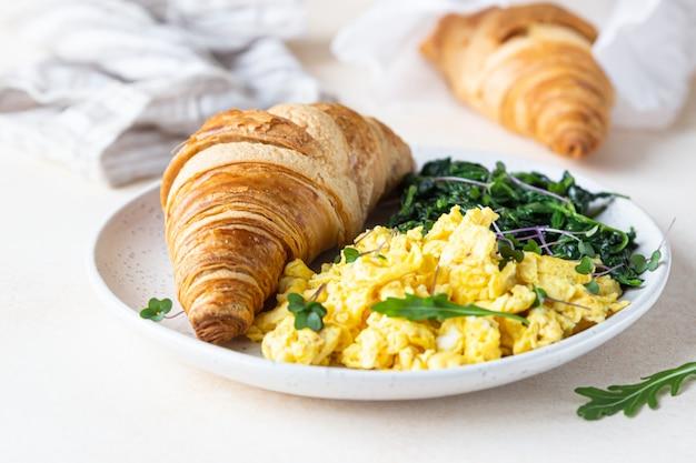 Круассан подается с яичницей и шпинатом на тарелке. завтрак.