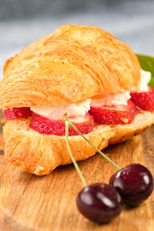 Croissant sweet sandwich with cream cheese and strawberries on a wooden board. useful breakfast. proper nutrition. french traditional dishes.