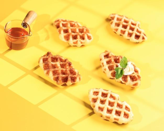 黄色いテーブルのマップルシロップとクロワッサンワッフル。 croffleは韓国のバイラルケーキです。コンセプトポップカラーフード、テキスト用コピースペース