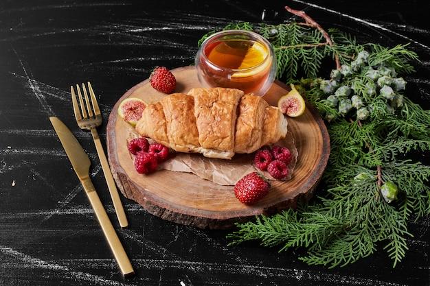 Croissant con frutti di bosco sul piatto di legno.