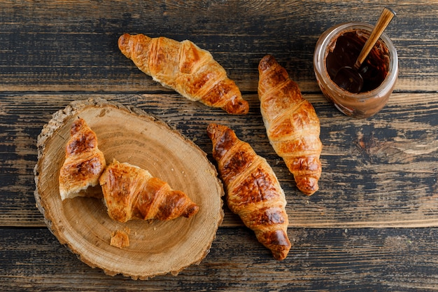 Croissant with chocolate cream flat lay on wooden and cutting board