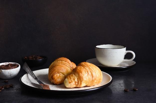 초콜릿 페이스트와 커피 한 잔을 곁들인 크루아상, 식탁에 딸기. 전통 간식 또는 아침 식사.