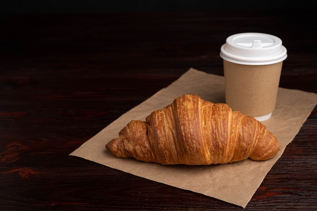 Croissant with coffee to go in a paper cup, take away breakfast