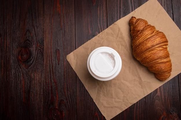 Круассан с кофе в бумажном стаканчике, завтрак на вынос