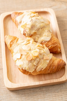 Croissant with cream and almonds on wood plate