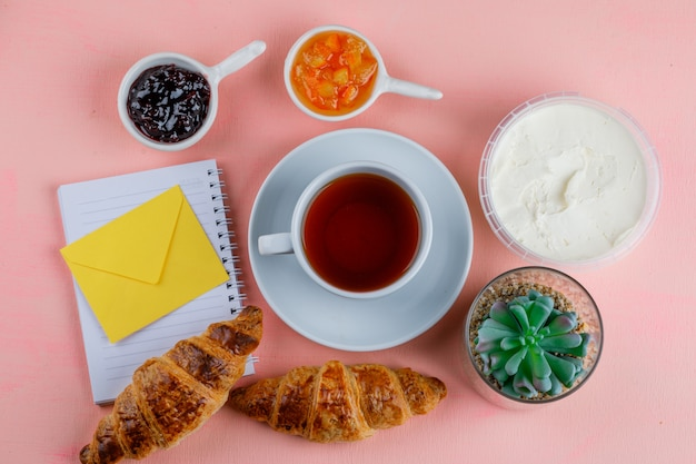 Croissant with cream cheese, tea, jam, plant, envelope, notebook on pink table, flat lay.