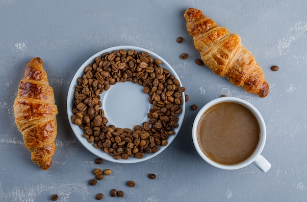 Croissant with cup of coffee, coffee beans, flat lay.