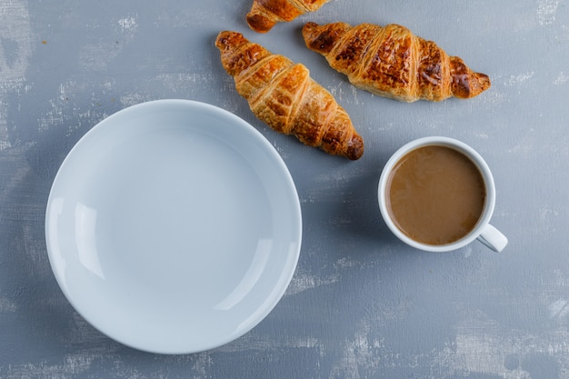 Croissant with cup of coffee, empty plate, flat lay.