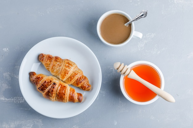 Croissant with cup of coffee, honey, dipper in a plate, flat lay.