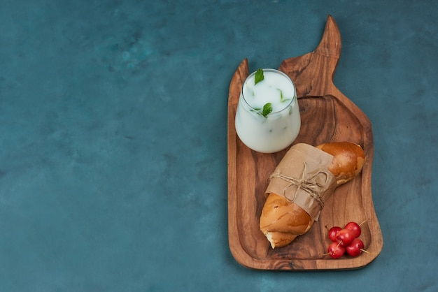 Croissant with a cup of milk and cherries.