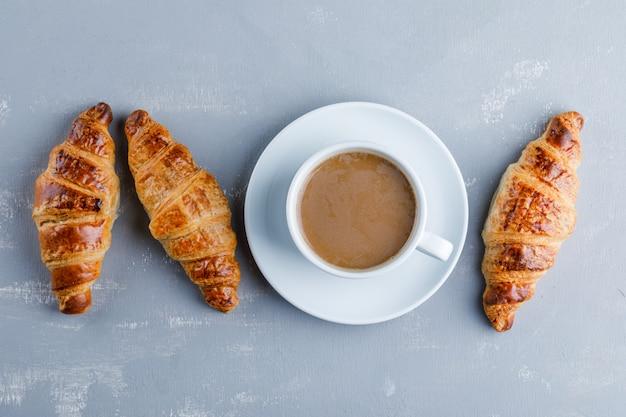 Круассан с чашкой кофе, плоский лежал.
