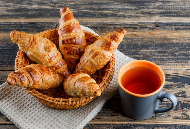 Croissant with cup of tea in a basket on wooden and kitchen towel, high angle view.