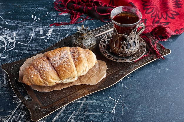 A croissant with a glass of tea.