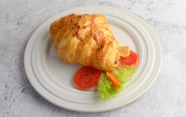 Croissant with hot dog on white dish