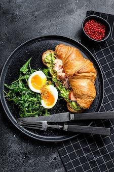Круассан с лососем горячего копчения, авокадо, рукколой и яйцом. черный фон. вид сверху