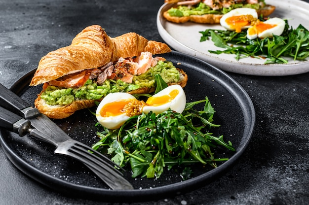 Croissant with hot smoked salmon, avacado, arugula and egg. black background. top view