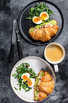 Croissant with hot smoked salmon, avacado, arugula and egg. top view