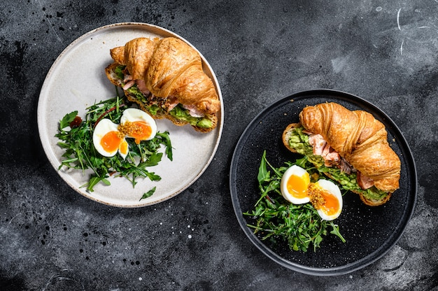 Croissant with hot smoked salmon, avacado, arugula and egg. top view.