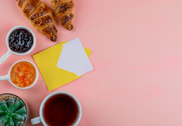 Croissant with jam, card in envelope, plant, tea flat lay on a pink table