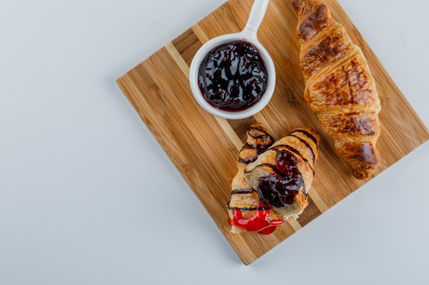 Croissant with jam flat lay on white and cutting board