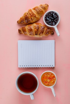 Croissant with jam, notebook, tea on pink table, top view.