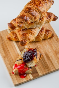 Croissant with jam on white and cutting board, high angle view.