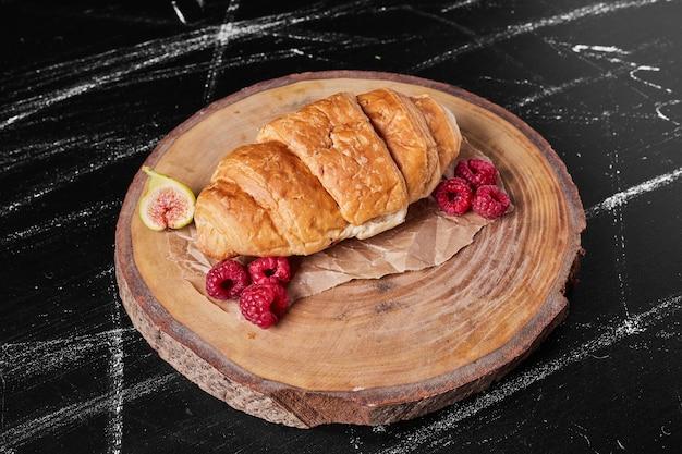 Croissant con lamponi sul piatto di legno.