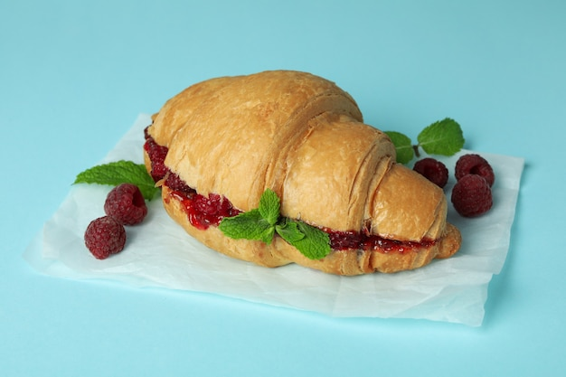 Croissant with raspberry jam on blue background