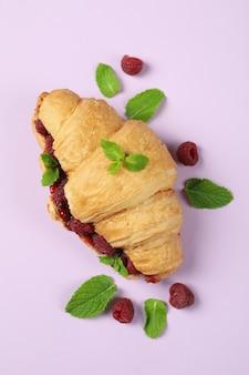 Croissant with raspberry jam on purple ã¢â€â‹background